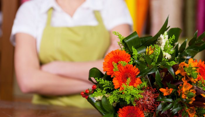 5b4c71016d8906 At the flower shop. Cropped image of young blond hair woman in apron  keeping arms