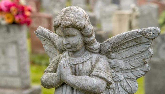 Praying angel in a cemetary with tombstones in the background
